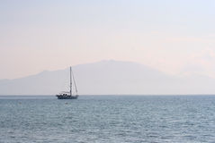 Yacht & Misty Mountain at dusk. Yacht moored in the bay of Keri, Zante, Greece royalty free stock image