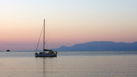 Yacht Moored in Bay at Dawn. Single masted yacht moored in Gulf of Corinth bay at dawn, soft pink light and view to Peloponnese mountains Stock Photography