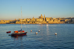 A yacht moored in the Marsamxett harbor with the Valletta capita. A view of yacht moored in the Marsamxett harbor with the Valletta capital city on the Royalty Free Stock Image