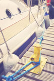 Yacht moored to a yellow bollard in marina. Royalty Free Stock Images