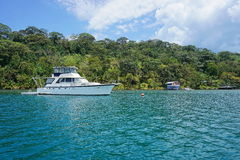 Yacht on mooring buoy with lush tropical coast Royalty Free Stock Photos
