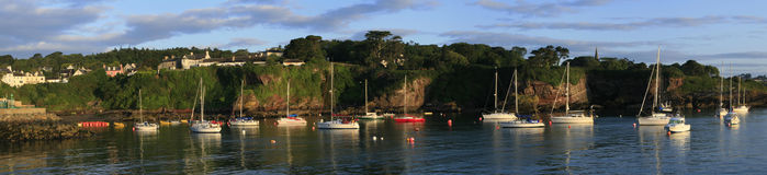 Yacht moorings in Dunmore East, Waterford, Ireland. Yachts outside harbour in Ireland, yachts on moorings plus sunlight. Panorama stock photos