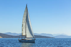 Yacht is moving along the coast. Sailing yacht in blue sea. Nature. Stock Photos