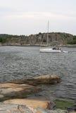 Yacht moving between the rocks. Swedish yacht passing between the rocks Royalty Free Stock Photography