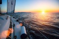 Yacht na regata da navigação no mar durante o por do sol Imagens de Stock