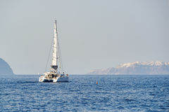 Yacht near Santorini sea coast Royalty Free Stock Images