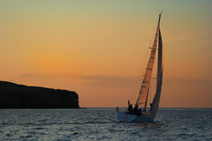 Yacht near to an island. The gold sky. The winner. A wave of a hand. It is Success stock photo