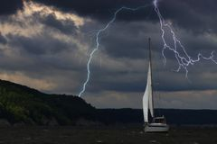 Yacht at the sea, comes nearer a thunderstorm with rain and lightning on background. Yacht at the ocean, comes nearer a thunderstorm with rain and lightning on royalty free stock photography