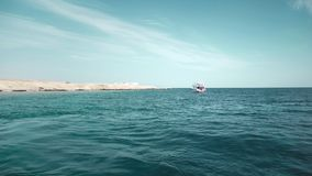 A yacht in the ocean with people on board. Against the background of a rocky desert beach. Diving and fishing. far view.  stock video