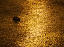 Yacht in ocean at sunset Stock Photo