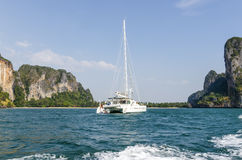 Yacht in the ocean, surrounded by cliffs. Royalty Free Stock Photo