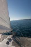 Yacht på det öppna hav. Ö på horisonten. Royaltyfria Bilder