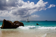 Yacht in paradise. Yacht in Seychelles with water splashing against a rock Stock Image
