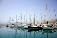 Yacht parking in harbor, harbor yacht club in Agios Nikolaos, Crete, Greece. Beautiful Yachts in blue sky background royalty free stock image