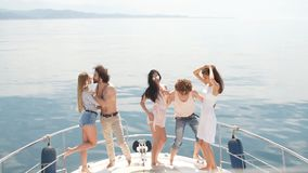 Yacht party with young people having a boat party, dancing on a bow of yacht deck