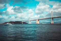 Yacht passes by the Bay Bridge royalty free stock images
