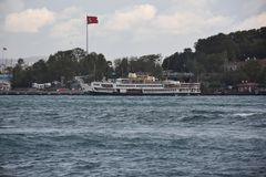Yacht passes in front of Topkapi Palace in Istanbul royalty free stock image