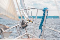 Yacht with people sails on the river on sails royalty free stock image