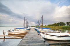 Yacht by pier on big lake Stock Photos