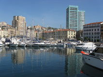 Yacht port in Savona. Yacht port, water reflection in haven and luxury buildings and skyscrapers in city of SAVONA in ITALY with clear blue sky in warm sunny Royalty Free Stock Images