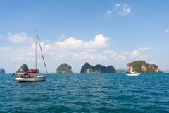 Yacht and power boat with limestone islands, Phang Nga Bay, Phuket, Thailand.  stock photos