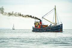Yacht and Puffer sailing on Moray Firth. An image of a yacht and SL VIC 32 sailing in the Moray Firth. The thick turbulent smoke is also a reminder of air stock photo
