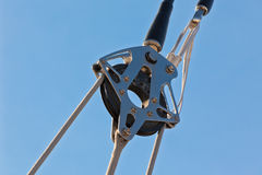 Yacht Pulley Blocks and Ropes. Against Blue Sky Background Stock Photo
