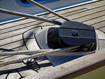 Yacht Pulley and Ropes. A modern rope pulley and attached and secured ropes on a wooden yacht deck. An example of ancient technology still in use Stock Photo
