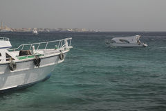 Yacht on the quay. Moored yacht and a boat in a coastal waters of Red Sea Royalty Free Stock Photos