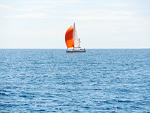 Yacht with red sail in blue Adriatic sea Royalty Free Stock Images