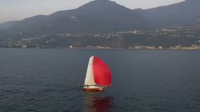 Yacht with red sail on the Garda Lake. Italy stock video footage