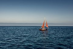 Yacht with a red sail in the sea royalty free stock photos