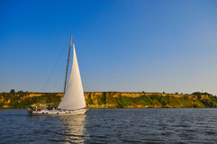 Yacht on river. Small yacht sailing on the river Dnipro, in Ukraine Royalty Free Stock Images