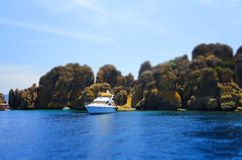 Yacht, rocks and blue sea, selective focus, effect tilt-shift Stock Photos