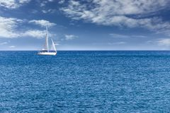 Yacht sailboat sailing alone on calm blue sea waters on a beautiful sunny day with blue sky and white clouds. White modern yacht sailboat sailing alone on calm Royalty Free Stock Photo