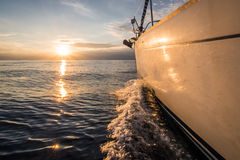 Yacht sailin towards sunset Stock Photo