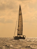 Yacht sailing against sunset Stock Images