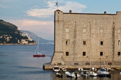 Yacht Sailing behind Fort in Dubrovnik Royalty Free Stock Image