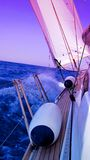 Yacht sailing in blue sea. Side view looking to front of yacht with colorful sail in blue sea Royalty Free Stock Photo