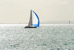 Yacht sailing with blue and white spinnaker Royalty Free Stock Image