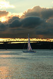 Yacht sailing by a bridge Stock Images