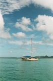 A yacht sailing on a clear day. With blue sky and green water Stock Images