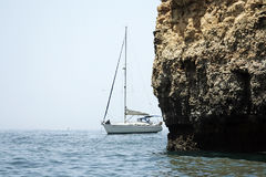 Yacht sailing by cliff Royalty Free Stock Images