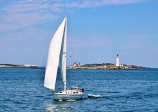 Yacht Sailing In Front Of Boston Harbor Lighthouse Royalty Free Stock Image