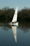A yacht sailing on a lake Stock Photos