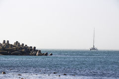 Yacht sailing near wave breakers Royalty Free Stock Images