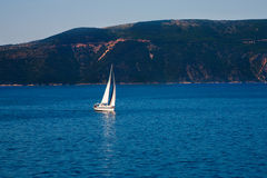 Yacht sailing in ocean. Scenic view of yacht sailing in ocean with Losinj island coastline in background, Croatia Stock Photo
