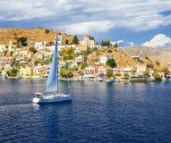 Yacht sailing past Symi island Royalty Free Stock Photos