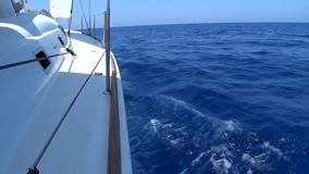 A view from the yacht`s deck to the bow and sails, close-up.S ide view with blue sea and waves.