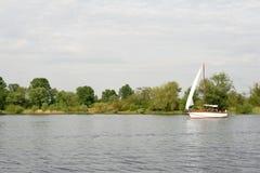 Yacht sailing a river Royalty Free Stock Photos